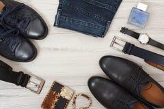 Två par av svarta skor för läderman` s, två bälten för män, jeans Arkivfoton