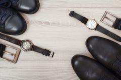 Två par av svarta skor för läderman` s, två bälten för män och tw Arkivfoton