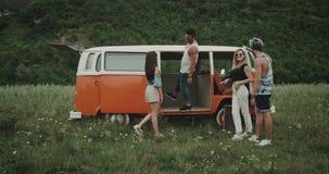 Två par har gyckel och dans i mitt av landskapet på picknicktid, höftvänner och den retro bussen 4K arkivfilmer