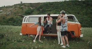 Två par har gyckel och dans i mitt av landskapet på picknicktid, höftvänner och den retro bussen 4K lager videofilmer