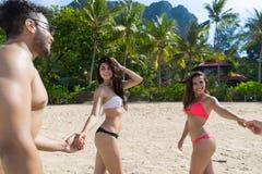 Två par på strandsommarsemestern, ungdomarförälskat gå, semesterort för hav för hav för händer för mankvinnainnehav Royaltyfri Fotografi