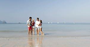 Två par som kör på stranden för att bevattna turister för lycklig gladlynt omfamning för folk för händer för manhållkvinna taland stock video