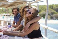Två par som ut hänger på sjösidan, ett kyssa för par Royaltyfria Bilder