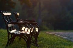 Två parkerar benchs med inga personer Arkivfoto