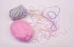 Två pastellfärgade rosa färger, vintergröna, guling och gröna Skeins för mintkaramell av garn arkivfoto