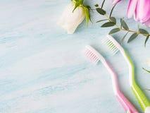 Två pastellfärgade tandborstar med blommaörter bakgrund colors vit yellow för den nya gröna tvätterifjädern Arkivfoto