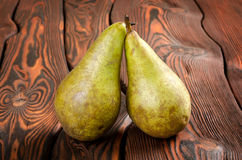 Två pears som är trä på en bakgrund arkivfoto