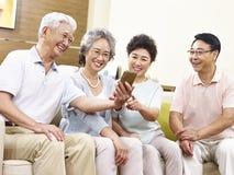 Två pensionärasiatpar som tar en selfie Royaltyfri Bild