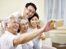 Två pensionärasiatpar som tar en selfie Royaltyfria Bilder