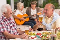 Två pensionärer som dricker öl arkivbild