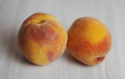Två persikor på den ljusa träbakgrunden arkivfoto