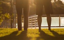 Två personer bredvid de i solnedgången Royaltyfri Foto