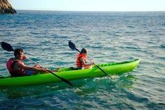 Två personer - en vuxen människa och ett barn avlar, och sonen i flytvästar seglar på uppblåsbara fartyg under vandring på sommar royaltyfri foto