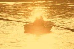 Två personer i en roddbåt blossade vid den guld- aftonsolen Royaltyfria Foton
