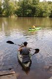 Två personer i kajaker på en flod i sommar arkivbilder