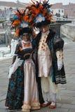 Två personer maskerade under karnevalet i Venedig poserar för fotoet nära en kanal arkivbild