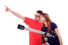 Två personer observerar till och med ett teleskop Arkivbild