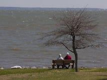 Två personer på bänk på Chesapeakefjärden royaltyfria foton