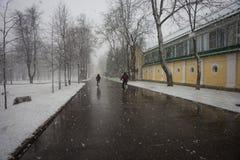 Två personer på cyklar som kör ut ur fenomen för ett väder - sno Arkivbild