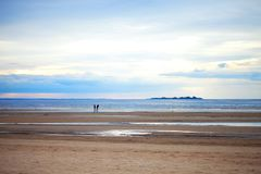 Två personer på den sandiga stranden i molnigt väder Arkivbild