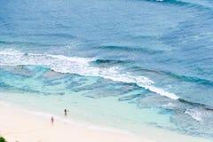 Två personer på sandstrandhavet royaltyfria foton