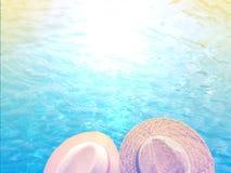Två personer på vattnets kant under solhattarna arkivfoto