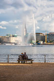 Två personer ser springbrunnen i mitten av Hamburg Royaltyfria Foton