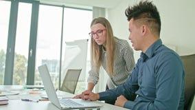 Två personer som diskuterar idéer genom att använda bärbara datorn stock video