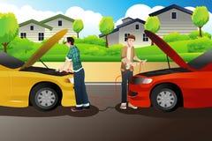 Två personer som försöker att hoppa start en bil Fotografering för Bildbyråer