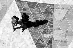 Två personer som går ner fyrkanten Arkivbild
