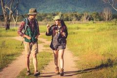 Två personer som går på banan i ängfält Man och kvinnlig handelsresande som ser dragningssiktspunkt Par äventyrar på överträffar fotografering för bildbyråer
