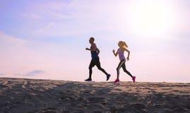 Två personer som joggar på solnedgången royaltyfri fotografi