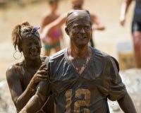 Två personer som mycket är smutsiga från gyttjagropen Royaltyfri Foto