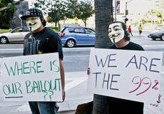 Två personer som protesterar i maskeringar rymmer tecken på upptar L.A. Fotografering för Bildbyråer