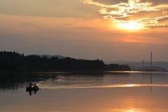 Två personer som ror en kanot på solnedgången Royaltyfria Foton