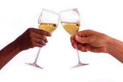 Två personer som rostar med exponeringsglas av vitt vin Arkivfoton