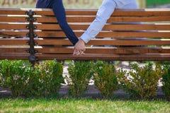 Två personer som rymmer händer, medan sitta på bänk Royaltyfri Fotografi