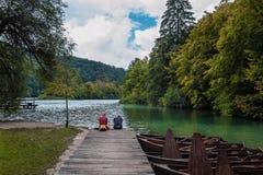 Två personer som sitter på en träpir över sjön i nedgången och att meditera, medan se vattnet royaltyfria foton