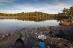 Två personer som sitter på kanten av sjödanandecoffe på ett stormkök, pinjeskog i vildmarken av Norge Royaltyfria Foton