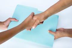 Två personer som skakar händer och utbyter dokument som ett tecken av överenskommelse royaltyfri fotografi