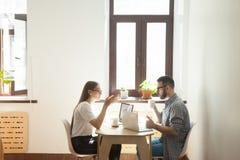 Två personer som tillsammans arbetar på ett projekt arkivbild