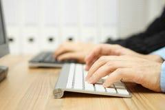 Två personer som tillsammans i regeringsställning arbetar på persondatorn med Royaltyfria Bilder