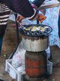 Två personer tar quial ägg för ` s som klart att äta ut ur ugnen Arkivfoton