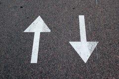 Två pilar på asfalt Tecken av tvåvägsgatan Arkivfoto