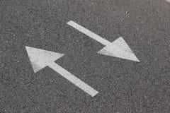 Två pilar på asfalt Tecken av tvåvägsgatan Royaltyfri Foto