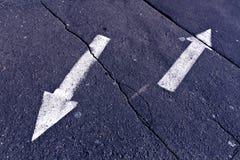 Två pilar på blått tonad knäckt asfaltyttersida Royaltyfria Bilder