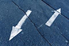 Två pilar på blått tonad knäckt asfaltyttersida Arkivfoton