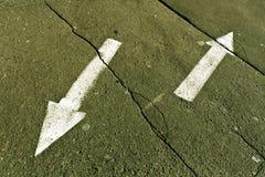 Två pilar på guling knäckt asfaltyttersida Royaltyfria Bilder