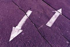 Två pilar på lilor tonad knäckt asfaltyttersida Arkivfoto