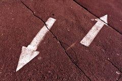 Två pilar på röd tonad sprucken asfaltyttersida Royaltyfri Bild